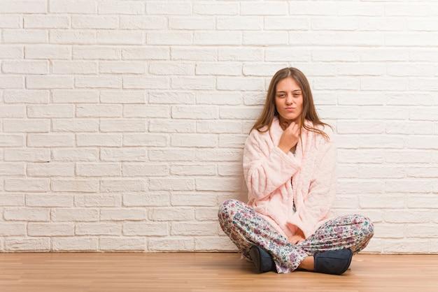Mulher jovem de pijama tossindo, doente devido a um vírus ou infecção