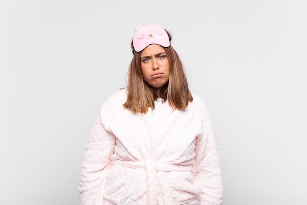 Mulher jovem de pijama, triste e chorona com uma expressão infeliz, chorando com uma atitude negativa e frustrada