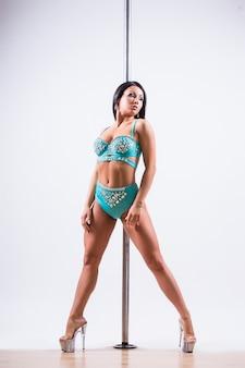 Mulher jovem de pole dance fazendo ginástica contra um fundo branco