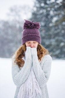 Mulher jovem de pulôver do lado de fora em um campo de neve