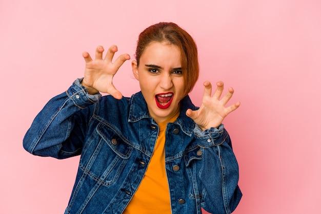 Mulher jovem de raça mista árabe mostrando garras imitando um gato, gesto agressivo.