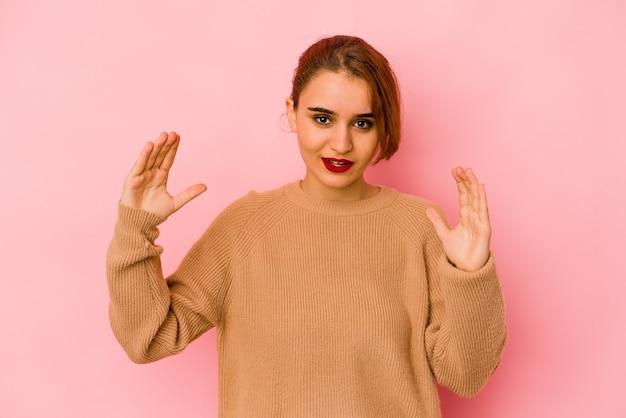 Mulher jovem de raça mista árabe segurando algo pequeno com os dedos indicadores, sorrindo e confiante.