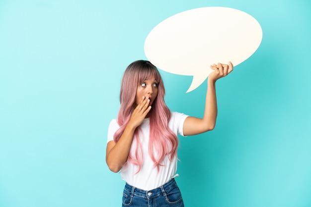 Mulher jovem de raça mista com cabelo rosa isolada em um fundo azul segurando um balão de fala vazio com expressão de surpresa