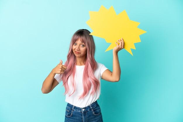 Mulher jovem de raça mista com cabelo rosa isolada em um fundo azul segurando um balão de fala vazio com o polegar para cima