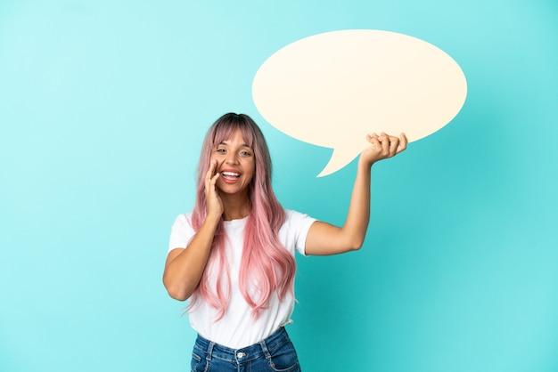 Mulher jovem de raça mista com cabelo rosa isolada em um fundo azul, segurando um balão de fala vazio e gritando