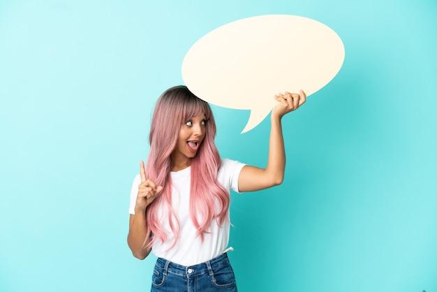 Mulher jovem de raça mista com cabelo rosa isolada em um fundo azul segurando um balão de fala vazio e pensando