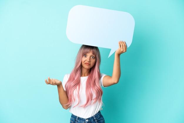 Mulher jovem de raça mista com cabelo rosa isolada em um fundo azul segurando um balão de fala vazio e tendo dúvidas