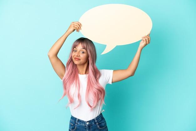 Mulher jovem de raça mista com cabelo rosa isolada em um fundo azul segurando um balão de fala vazio