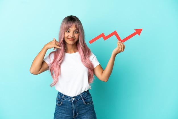 Mulher jovem de raça mista com cabelo rosa isolada em um fundo azul segurando uma seta ascendente e fazendo gesto de telefone