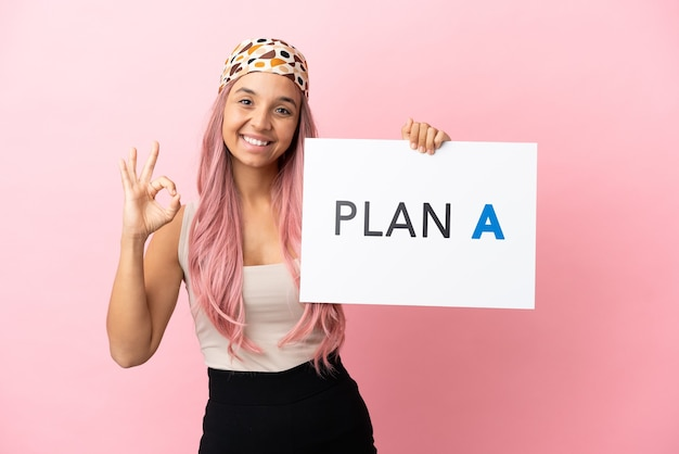 Mulher jovem de raça mista com cabelo rosa isolada em um fundo rosa segurando um cartaz com a mensagem plano a com o sinal de ok