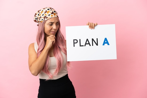 Mulher jovem de raça mista com cabelo rosa isolada em um fundo rosa segurando um cartaz com a mensagem plano a e pensando