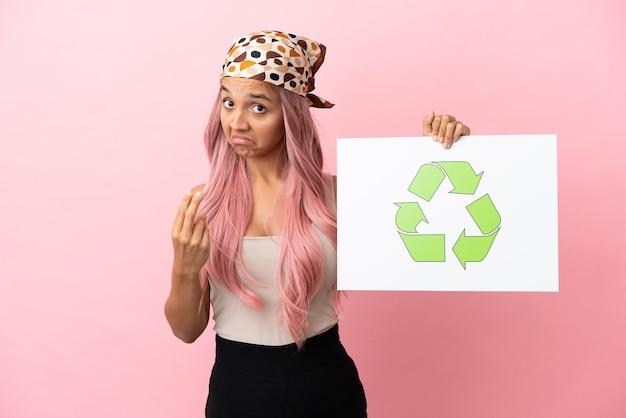 Mulher jovem de raça mista com cabelo rosa isolada em um fundo rosa segurando um cartaz com o ícone de reciclagem e fazendo gesto próximo
