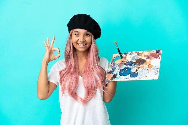 Mulher jovem de raça mista com cabelo rosa segurando uma paleta isolada em um fundo azul e mostrando um sinal de ok com os dedos