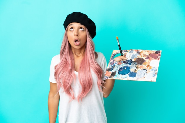 Mulher jovem de raça mista com cabelo rosa segurando uma paleta isolada em um fundo azul olhando para cima e com expressão de surpresa