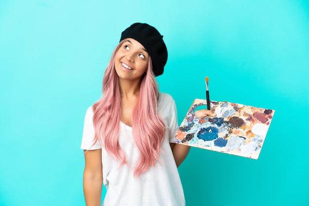 Mulher jovem de raça mista com cabelo rosa segurando uma paleta isolada em um fundo azul pensando uma ideia enquanto olha para cima