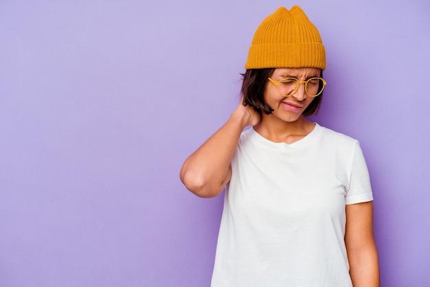 Mulher jovem de raça mista com um boné de lã isolado no fundo roxo, tocando a parte de trás da cabeça, pensando e fazendo uma escolha.