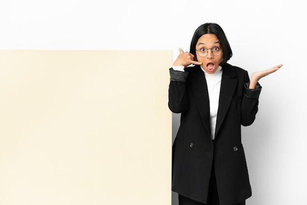 Mulher jovem de raça mista com um grande banner sobre fundo isolado fazendo gestos de telefone e duvidando