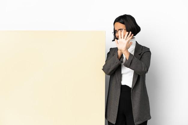 Mulher jovem de raça mista com um grande banner sobre um fundo isolado nervoso, estendendo as mãos para a frente