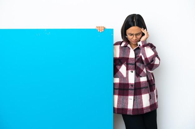 Mulher jovem de raça mista com um grande cartaz azul isolado no fundo branco com dor de cabeça