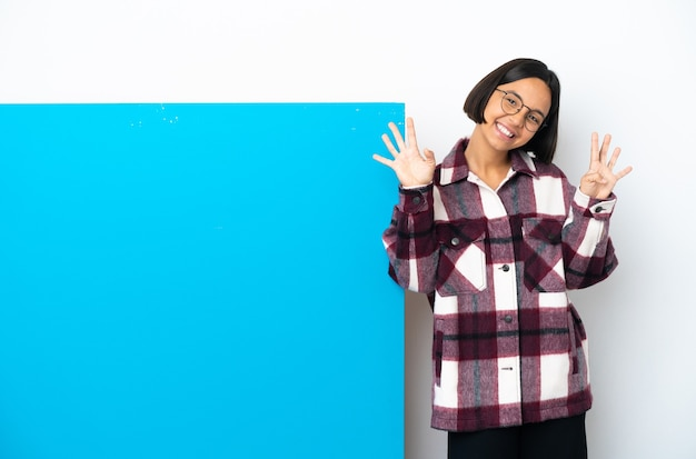 Mulher jovem de raça mista com um grande cartaz azul isolado no fundo branco, contando nove com os dedos