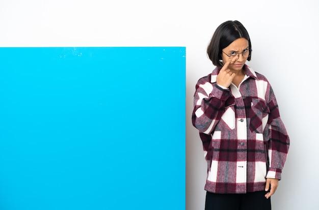 Mulher jovem de raça mista com um grande cartaz azul isolado no fundo branco mostrando algo