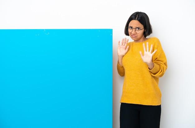 Mulher jovem de raça mista com um grande cartaz azul isolado no fundo branco nervosa esticando as mãos para a frente