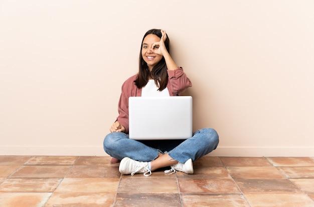 Mulher jovem de raça mista com um laptop sentada no chão, mostrando sinal de ok com os dedos
