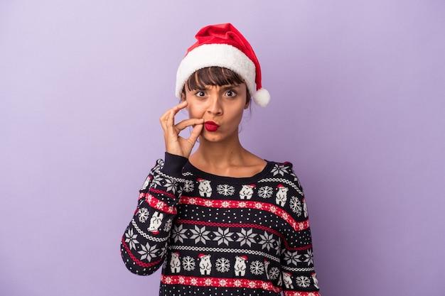 Mulher jovem de raça mista comemorando o natal isolado em um fundo roxo com os dedos nos lábios, mantendo um segredo.