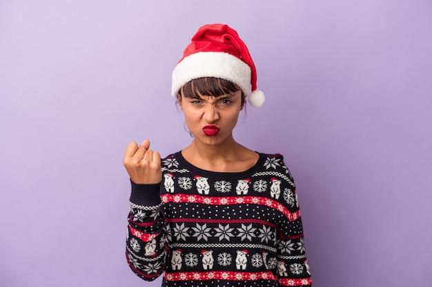 Mulher jovem de raça mista comemorando o natal isolado no fundo roxo, mostrando o punho para a câmera, expressão facial agressiva.