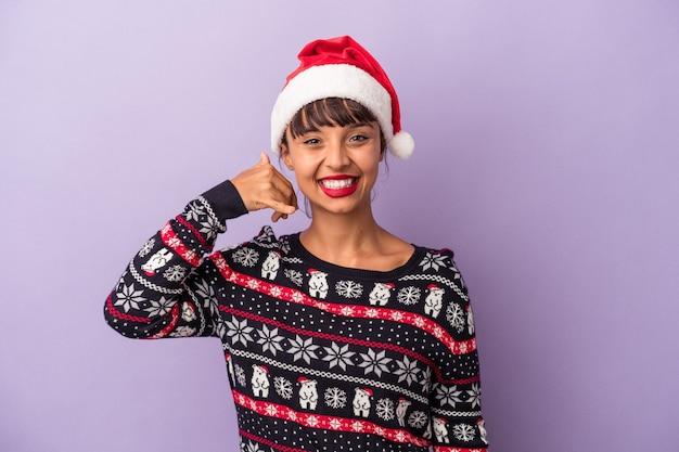 Mulher jovem de raça mista comemorando o natal isolado no fundo roxo, mostrando um gesto de chamada de telefone móvel com os dedos.