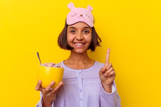 Mulher jovem de raça mista comendo cereais usando um pijama isolado na parede amarela, mostrando o número um com o dedo.