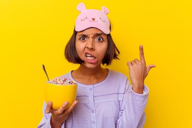 Mulher jovem de raça mista comendo cereais usando um pijama isolado na parede amarela, mostrando um gesto de decepção com o dedo indicador.