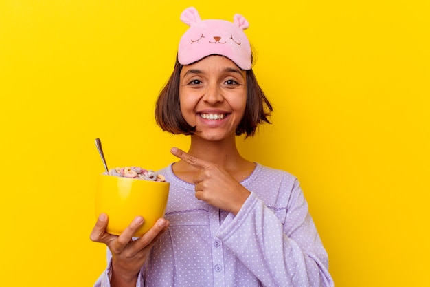 Mulher jovem de raça mista comendo cereais usando um pijama isolado na parede amarela, sorrindo e apontando para o lado, mostrando algo no espaço em branco.