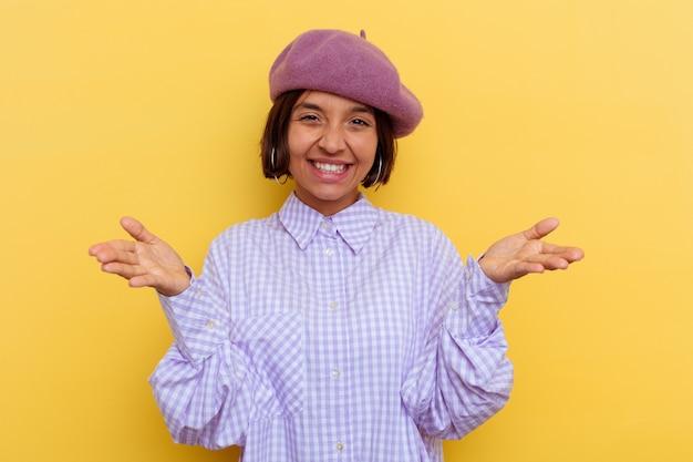 Mulher jovem de raça mista de boina isolada em fundo amarelo se sente confiante em dar um abraço para a câmera.