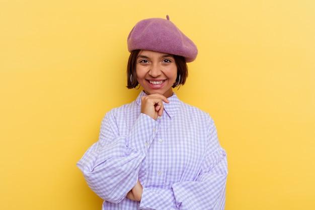 Mulher jovem de raça mista de boina isolada na parede amarela, sorrindo feliz e confiante, tocando o queixo com a mão.
