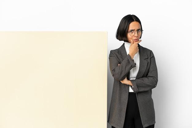 Mulher jovem de raça mista de negócios com um grande banner isolado fundo tendo dúvidas