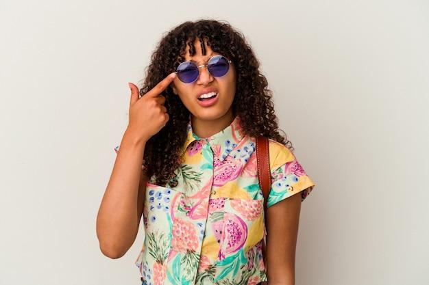 Mulher jovem de raça mista de óculos escuros, tirando férias isoladas, mostrando um gesto de decepção com o dedo indicador.
