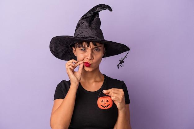 Mulher jovem de raça mista disfarçada de bruxa, isolada em um fundo roxo com os dedos nos lábios, mantendo um segredo.