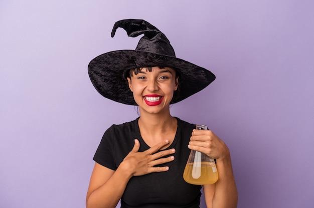 Mulher jovem de raça mista disfarçada de bruxa, segurando a poção isolada no fundo roxo, ri alto, mantendo a mão no peito.
