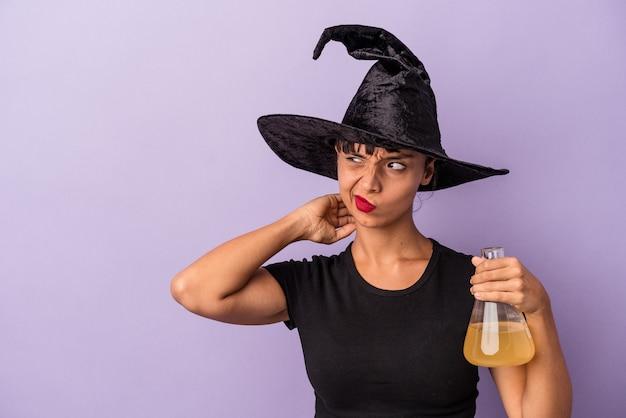 Mulher jovem de raça mista disfarçada de bruxa, segurando a poção isolada no fundo roxo, tocando a parte de trás da cabeça, pensando e fazendo uma escolha.