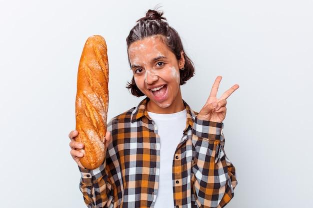 Mulher jovem de raça mista, fazendo pão isolado no fundo branco, alegre e despreocupada, mostrando um símbolo de paz com os dedos.