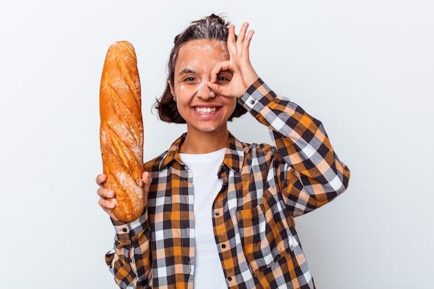 Mulher jovem de raça mista, fazendo pão isolado no fundo branco, animado, mantendo o gesto ok no olho.