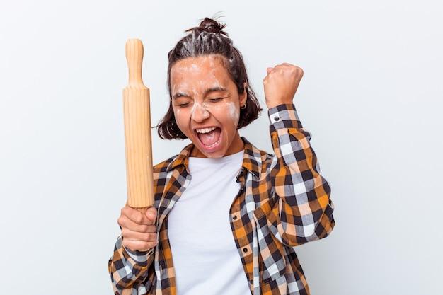 Mulher jovem de raça mista fazendo pão isolado no fundo branco, levantando o punho após uma vitória, o conceito de vencedor.
