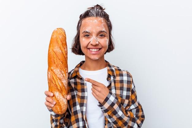 Mulher jovem de raça mista fazendo pão isolado no fundo branco, sorrindo e apontando para o lado, mostrando algo no espaço em branco.