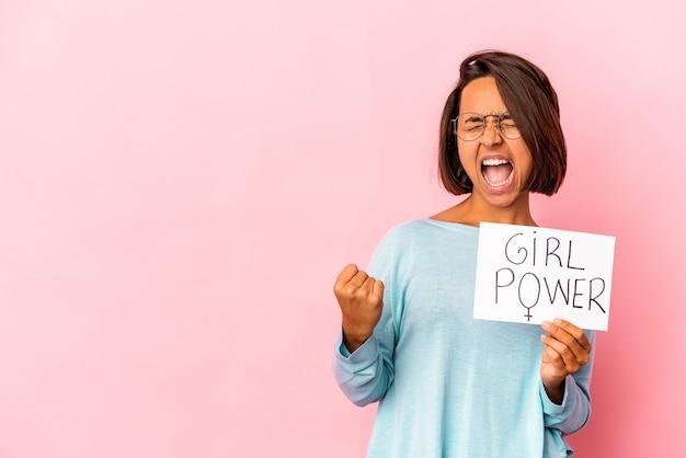 Mulher jovem de raça mista hispânica segurando um cartaz de mensagem de poder feminino levantando o punho após uma vitória, o conceito de vencedor.