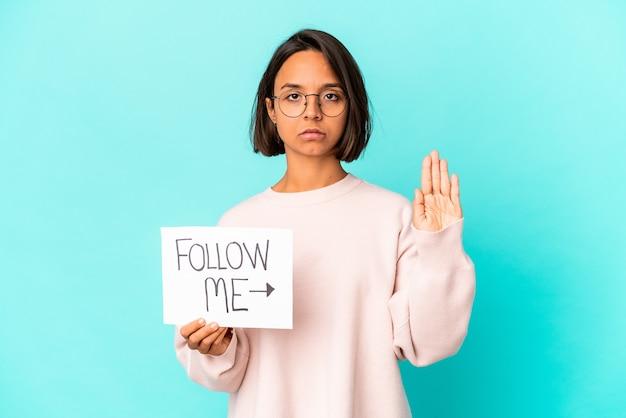 Mulher jovem de raça mista hispânica segurando um cartaz de siga-me em pé com a mão estendida, mostrando o sinal de pare, impedindo você.