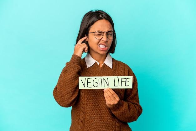 Mulher jovem de raça mista hispânica segurando um cartaz de vida vegana cobrindo as orelhas com as mãos.