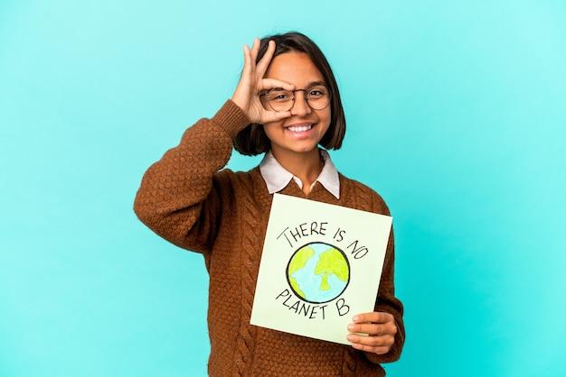 Mulher jovem de raça mista hispânica segurando um planeta salvar cartaz animado mantendo o gesto ok no olho.