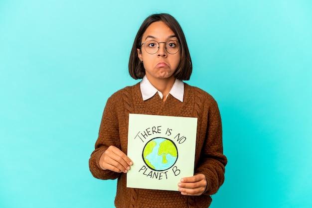 Mulher jovem de raça mista hispânica segurando um planeta salvar cartaz encolhe os ombros e abre os olhos confusos.