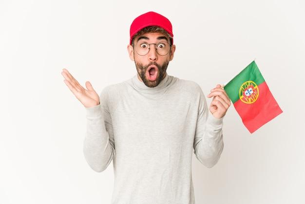 Mulher jovem de raça mista hispânica segurando uma bandeira de portugal surpresa e chocada.